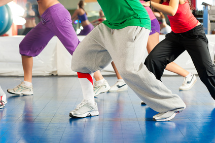 Fitness - Young people (only legs to be seen) doing Zumba training or dance workout in a gym